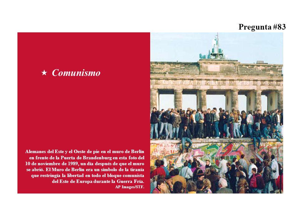 Alemanes del Este y el Oeste de pie en el muro de Berlín en frente de la Puerta de Brandenburg en esta foto del 10 de noviembre de 1989, un día después de que el muro se abrió.