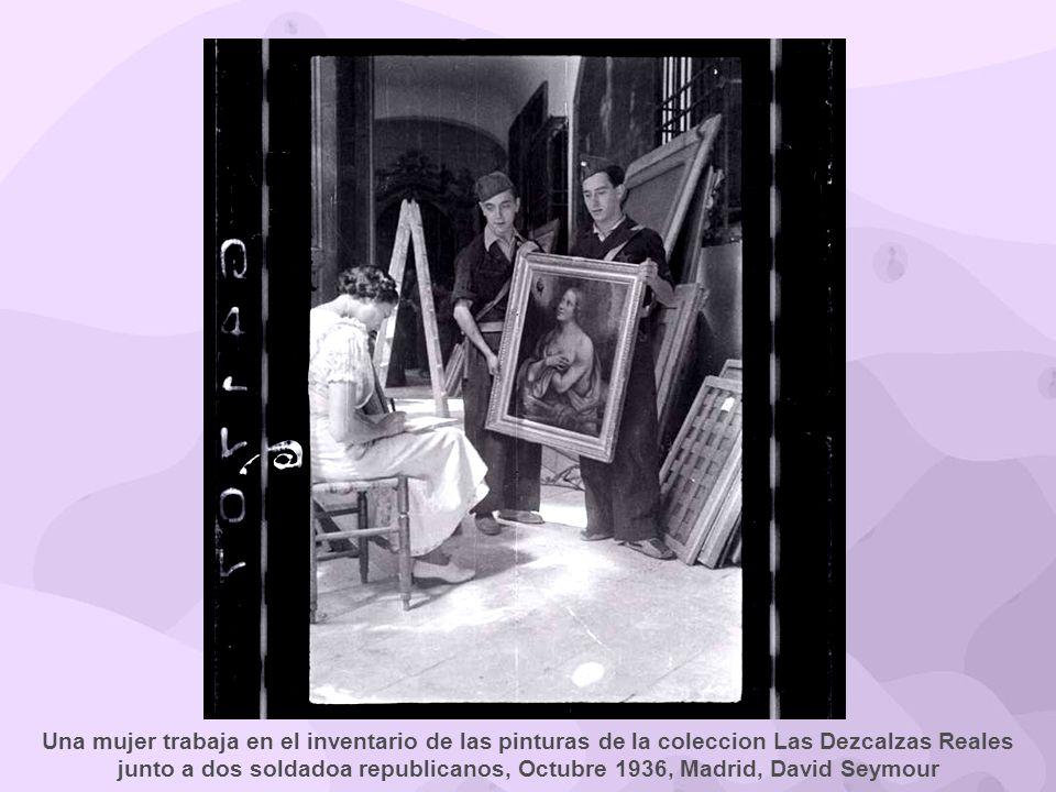Una mujer trabaja en el inventario de las pinturas de la coleccion Las Dezcalzas Reales junto a dos soldadoa republicanos, Octubre 1936, Madrid, David Seymour