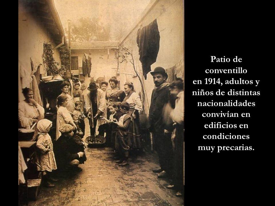 Patio de conventillo en 1914, adultos y niños de distintas nacionalidades convivían en edificios en condiciones muy precarias.