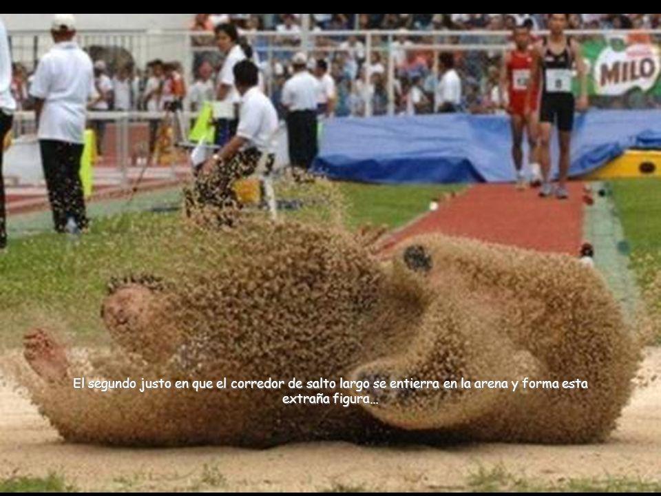 El segundo justo en que el corredor de salto largo se entierra en la arena y forma esta extraña figura…