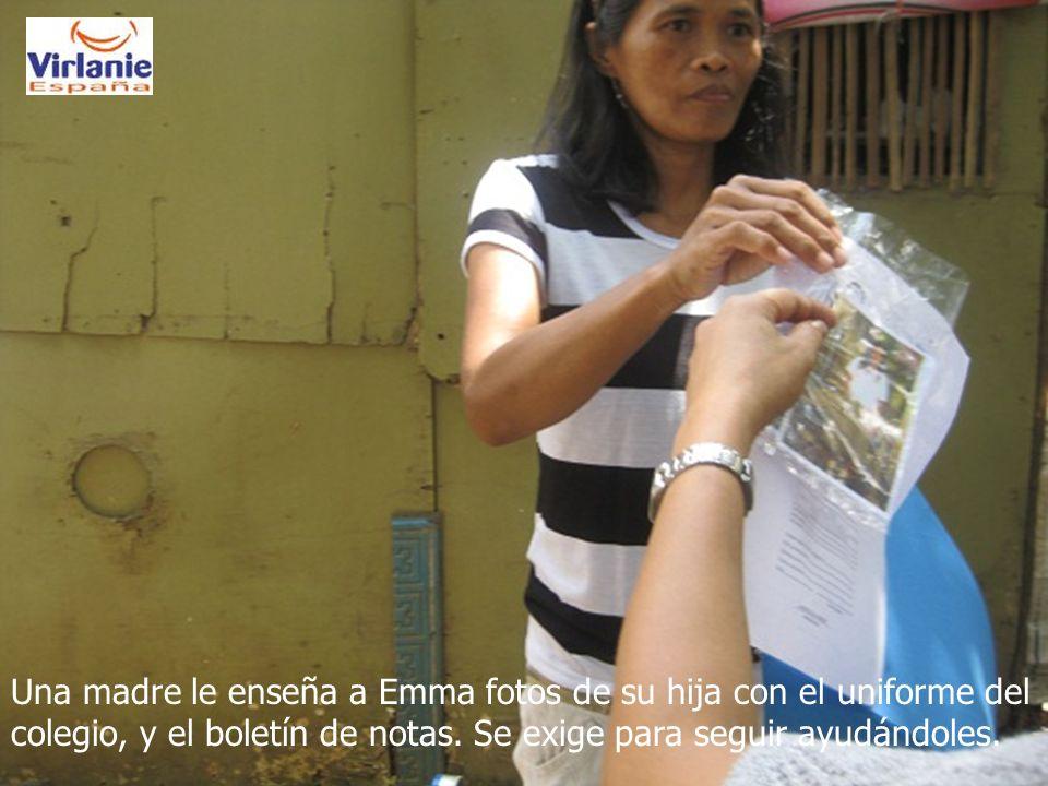 Una madre le enseña a Emma fotos de su hija con el uniforme del colegio, y el boletín de notas.