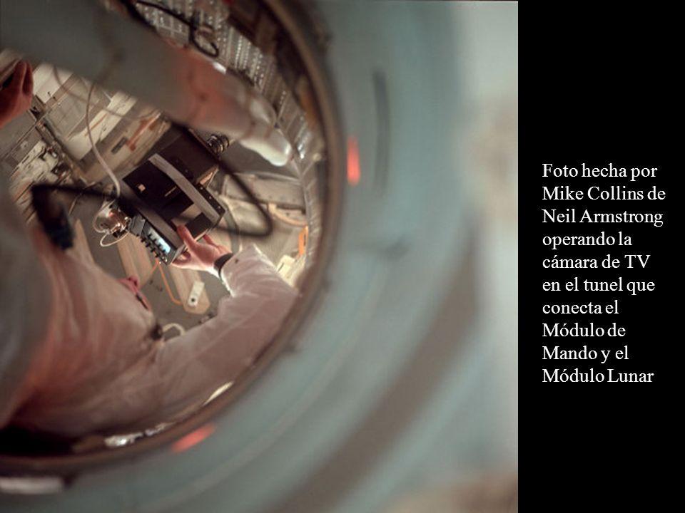 Foto hecha por Mike Collins de Neil Armstrong operando la cámara de TV en el tunel que conecta el Módulo de Mando y el Módulo Lunar