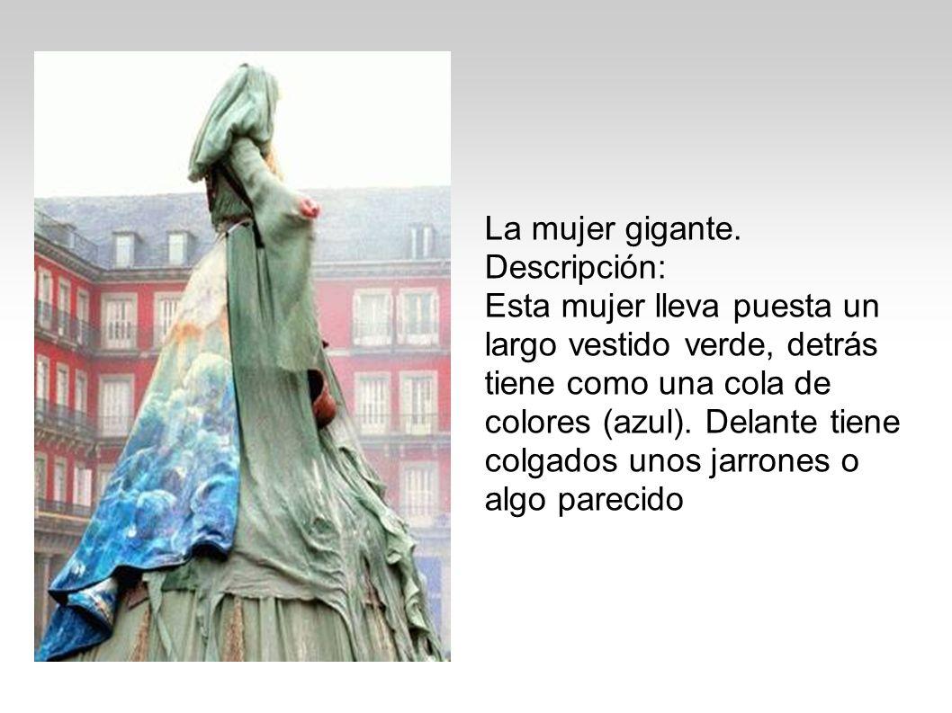 La mujer gigante. Descripción: Esta mujer lleva puesta un largo vestido verde, detrás tiene como una cola de colores (azul). Delante tiene colgados un