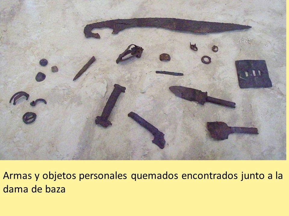 Armas y objetos personales quemados encontrados junto a la dama de baza