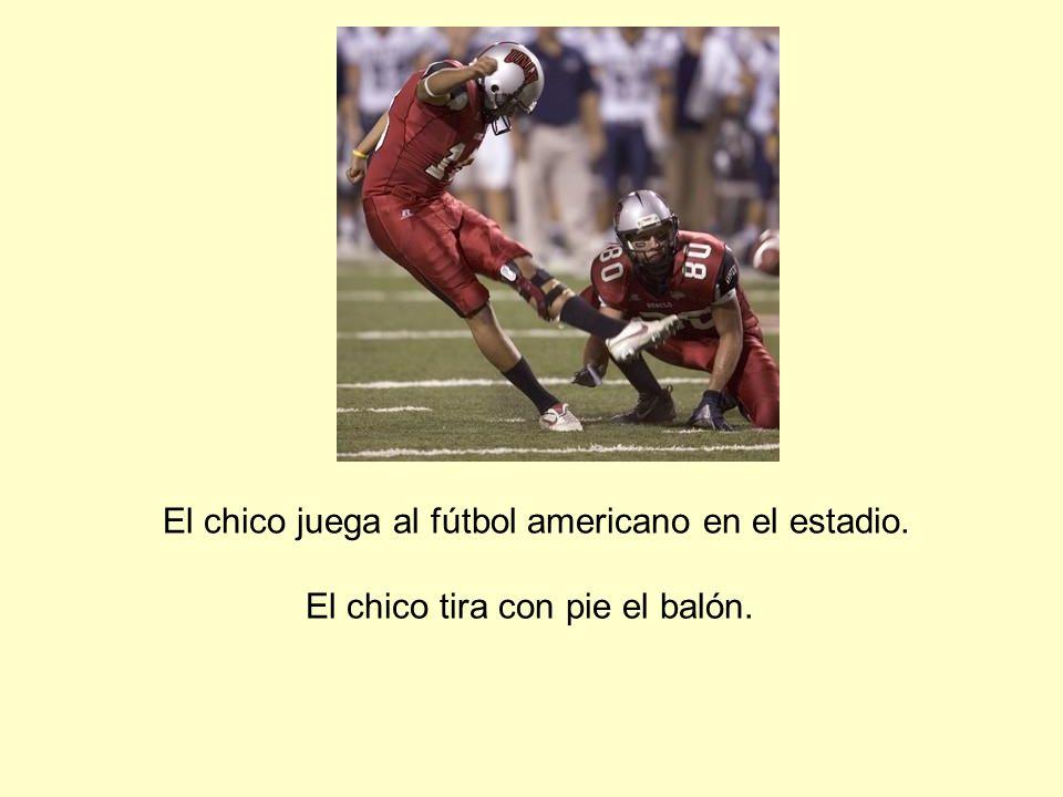 El chico juega al fútbol americano en el estadio. El chico tira con pie el balón.