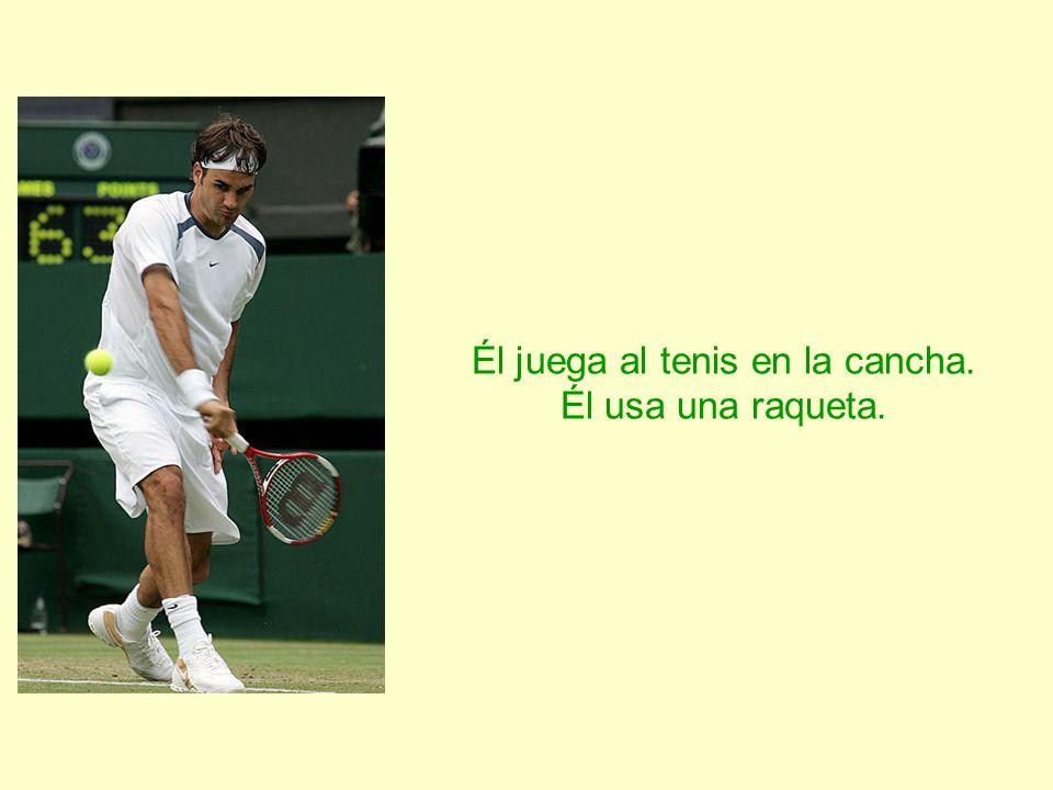 Él juega al tenis en la cancha. Él usa una raqueta.