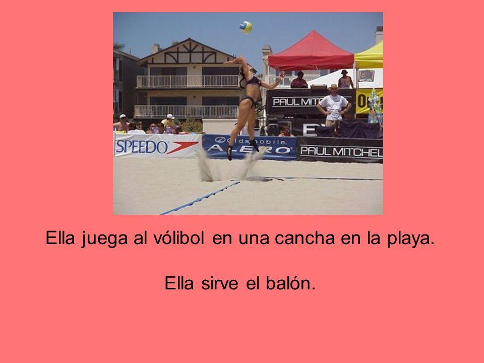 Ella juega al vólibol en una cancha en la playa. Ella sirve el balón.