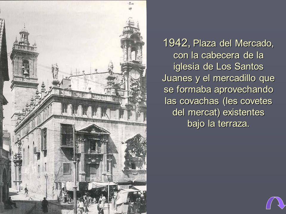 1942, Plaza del Mercado, con la cabecera de la iglesia de Los Santos Juanes y el mercadillo que se formaba aprovechando las covachas (les covetes del mercat) existentes bajo la terraza.