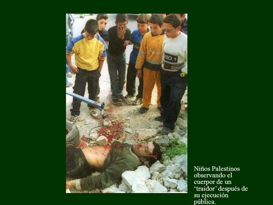 Niños Palestinos observando el cuerpor de un traidor después de su ejecución pública.
