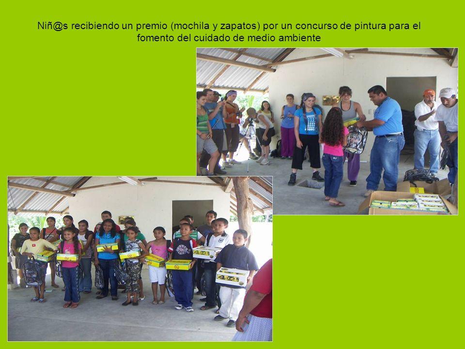 Niñ@s recibiendo un premio (mochila y zapatos) por un concurso de pintura para el fomento del cuidado de medio ambiente