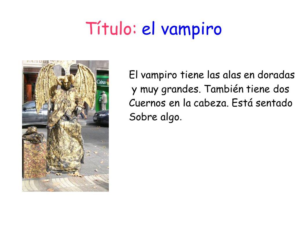 Título: el vampiro El vampiro tiene las alas en doradas y muy grandes. También tiene dos Cuernos en la cabeza. Está sentado Sobre algo.