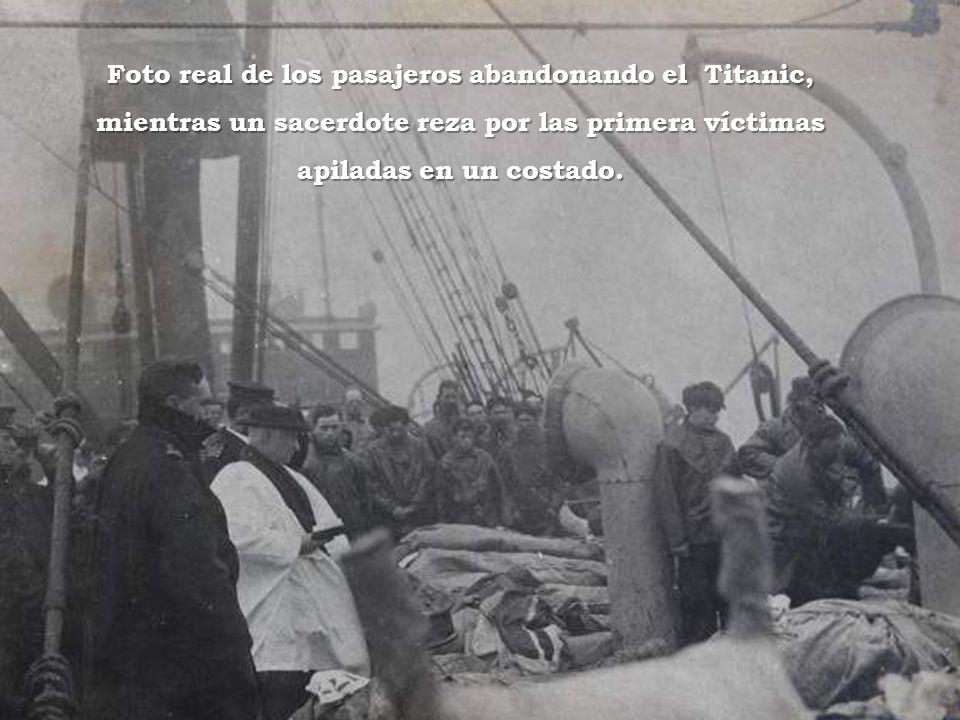 Foto real de los pasajeros abandonando el Titanic, mientras un sacerdote reza por las primera víctimas apiladas en un costado.