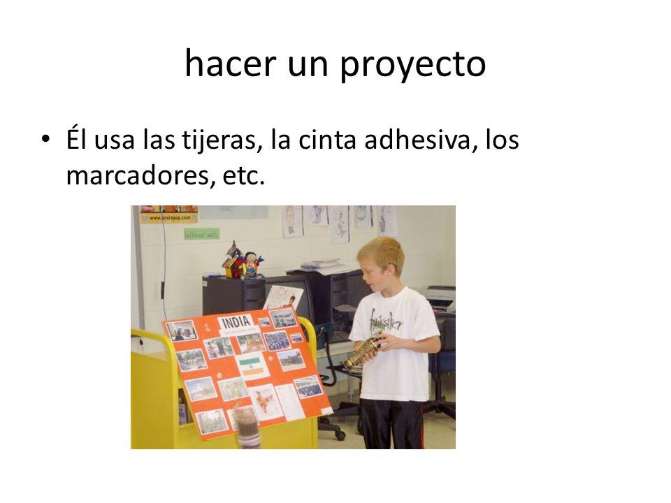 hacer un proyecto Él usa las tijeras, la cinta adhesiva, los marcadores, etc.