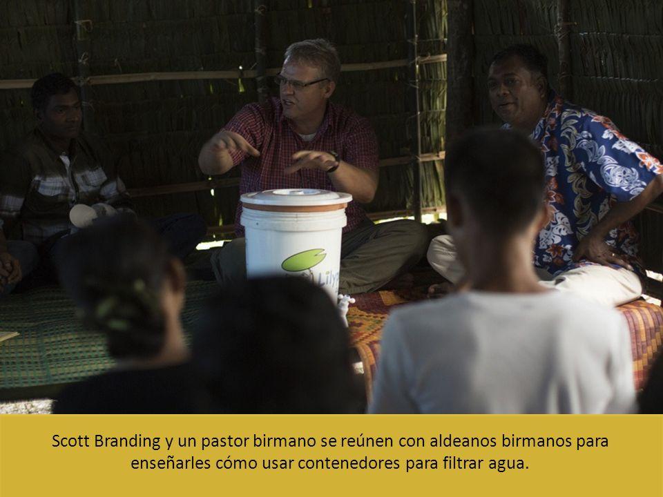 Scott Branding y un pastor birmano se reúnen con aldeanos birmanos para enseñarles cómo usar contenedores para filtrar agua.