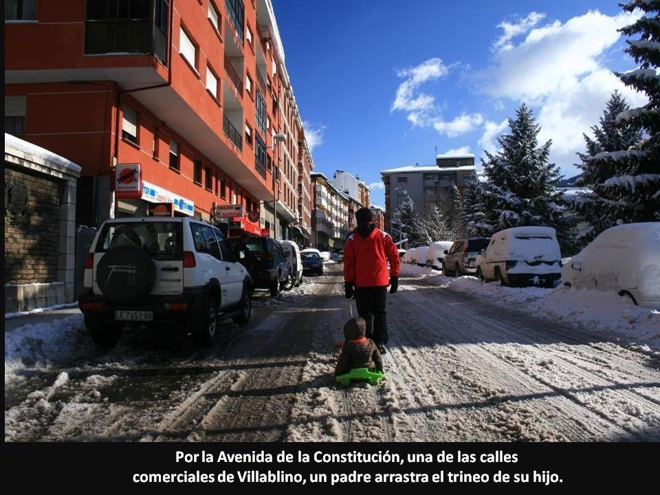 Por la Avenida de la Constitución, una de las calles comerciales de Villablino, un padre arrastra el trineo de su hijo.