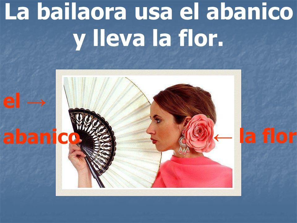 La bailaora usa el abanico y lleva la flor. el abanico la flor