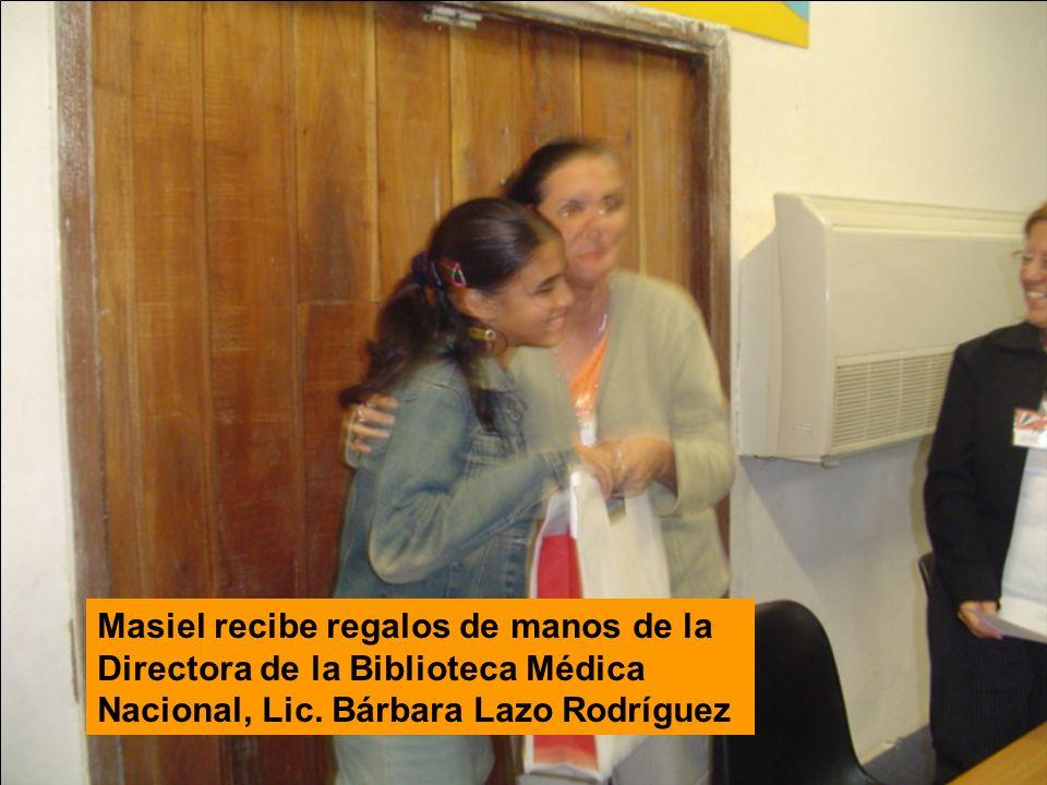 Masiel recibe regalos de manos de la Directora de la Biblioteca Médica Nacional, Lic.