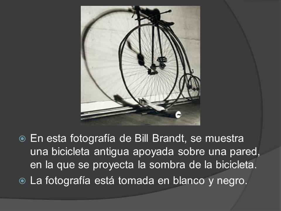 En esta fotografía de Bill Brandt, se muestra una bicicleta antigua apoyada sobre una pared, en la que se proyecta la sombra de la bicicleta. La fotog