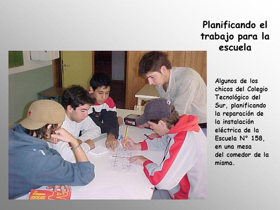 Planificando el trabajo para la escuela Algunos de los chicos del Colegio Tecnológico del Sur, planificando la reparación de la instalación eléctrica de la Escuela N° 158, en una mesa del comedor de la misma.