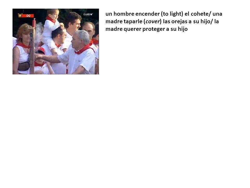 un hombre encender (to light) el cohete/ una madre taparle (cover) las orejas a su hijo/ la madre querer proteger a su hijo