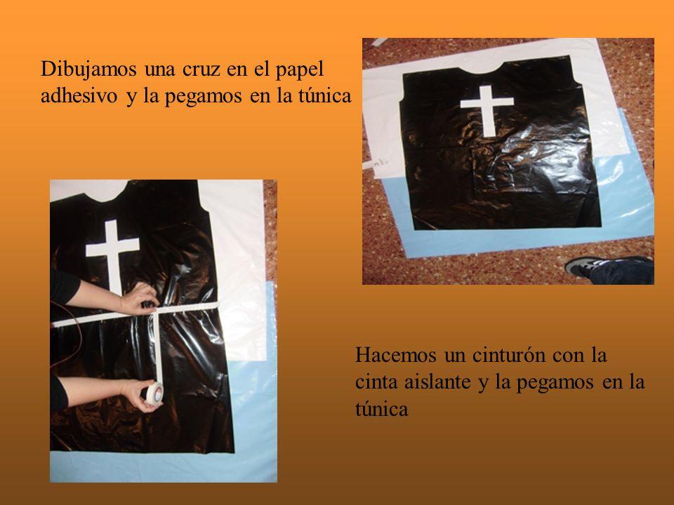 Dibujamos una cruz en el papel adhesivo y la pegamos en la túnica Hacemos un cinturón con la cinta aislante y la pegamos en la túnica
