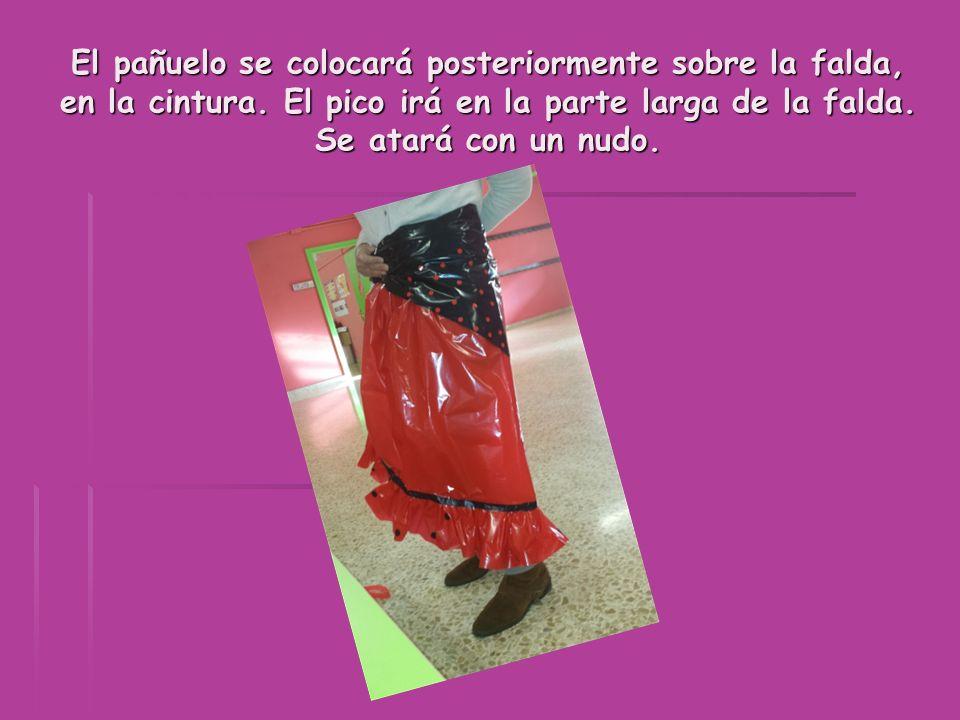 El pañuelo se colocará posteriormente sobre la falda, en la cintura. El pico irá en la parte larga de la falda. Se atará con un nudo.