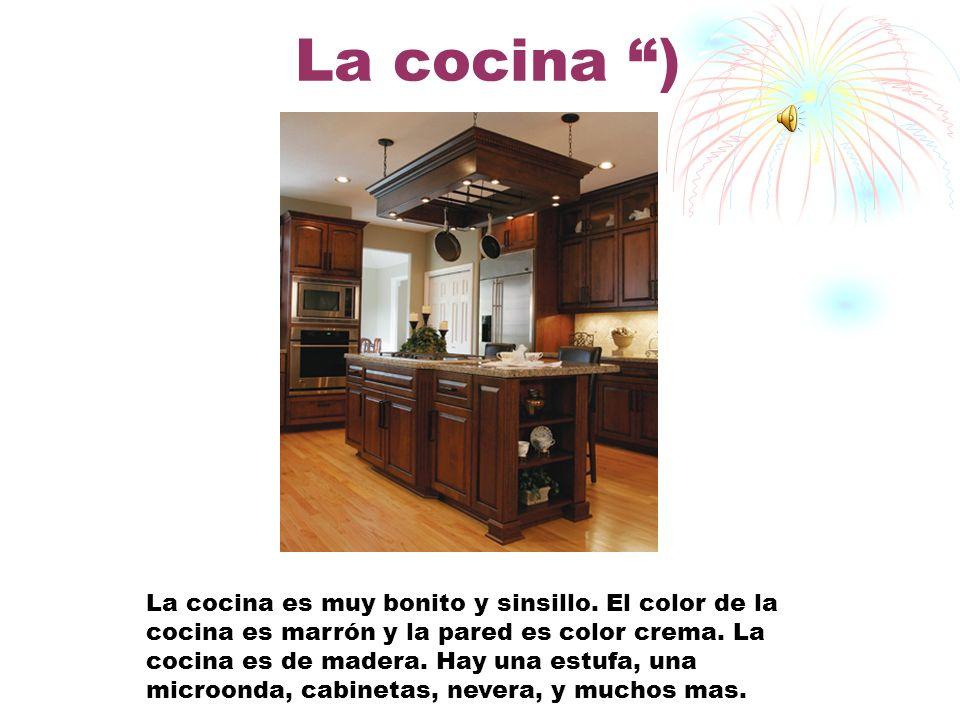 El comedor ) El comedor es modelo y bonito. El comedor es color crema y marrón. Hay dos lamparas colgando del techo. Una mesa marrón, un cuardo, y una