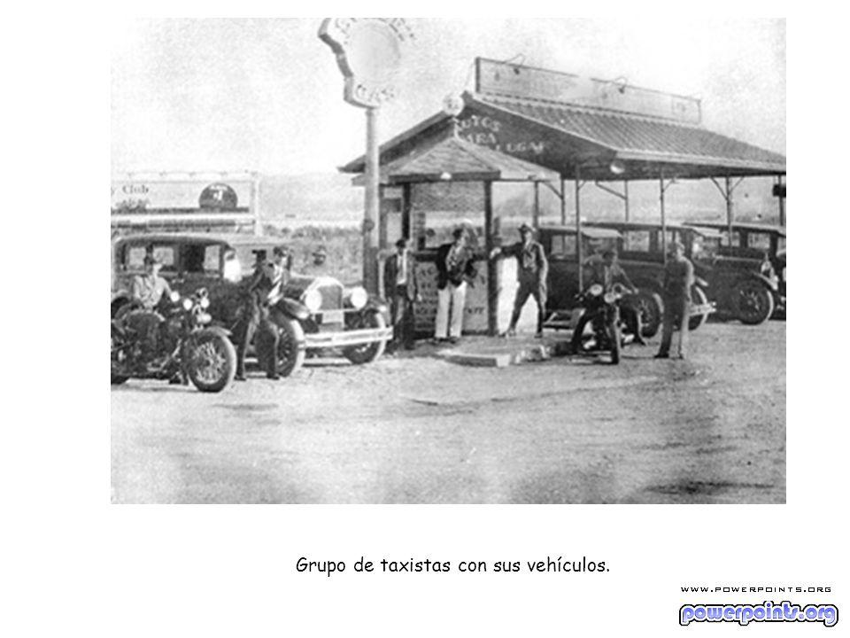Grupo de taxistas con sus vehículos.