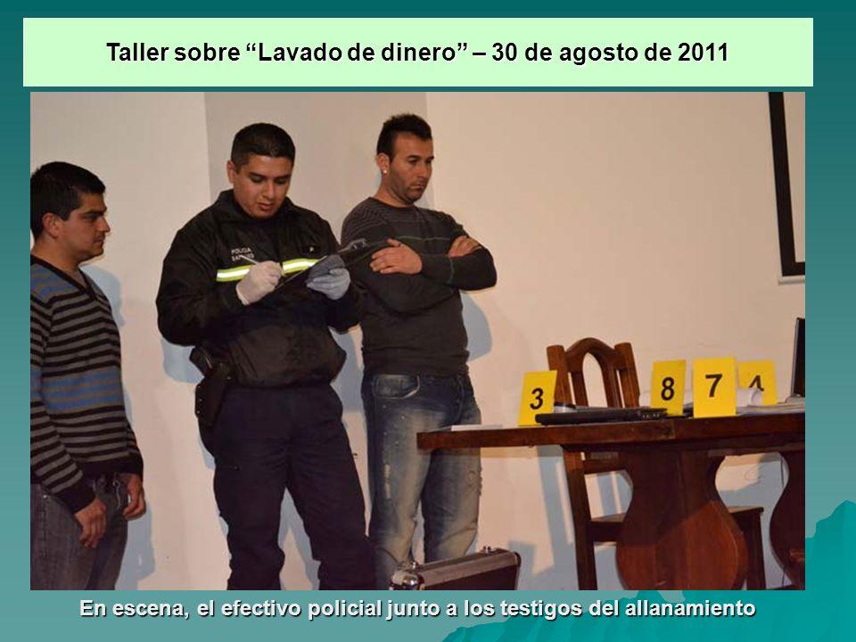En escena, el efectivo policial junto a los testigos del allanamiento Taller sobre Lavado de dinero – 30 de agosto de 2011