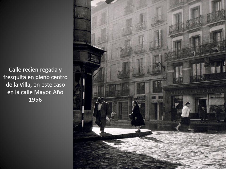 Calle recien regada y fresquita en pleno centro de la Villa, en este caso en la calle Mayor. Año 1956
