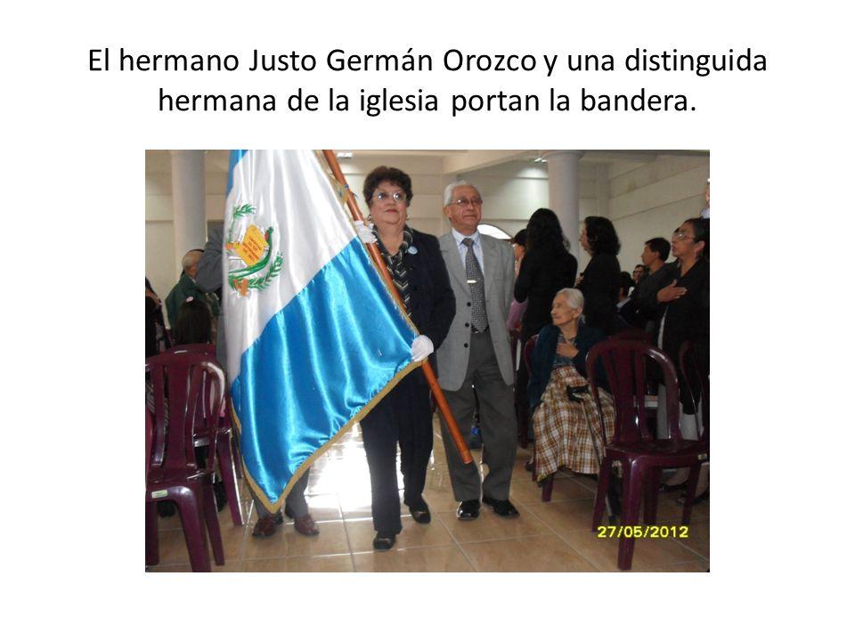 El hermano Justo Germán Orozco y una distinguida hermana de la iglesia portan la bandera.