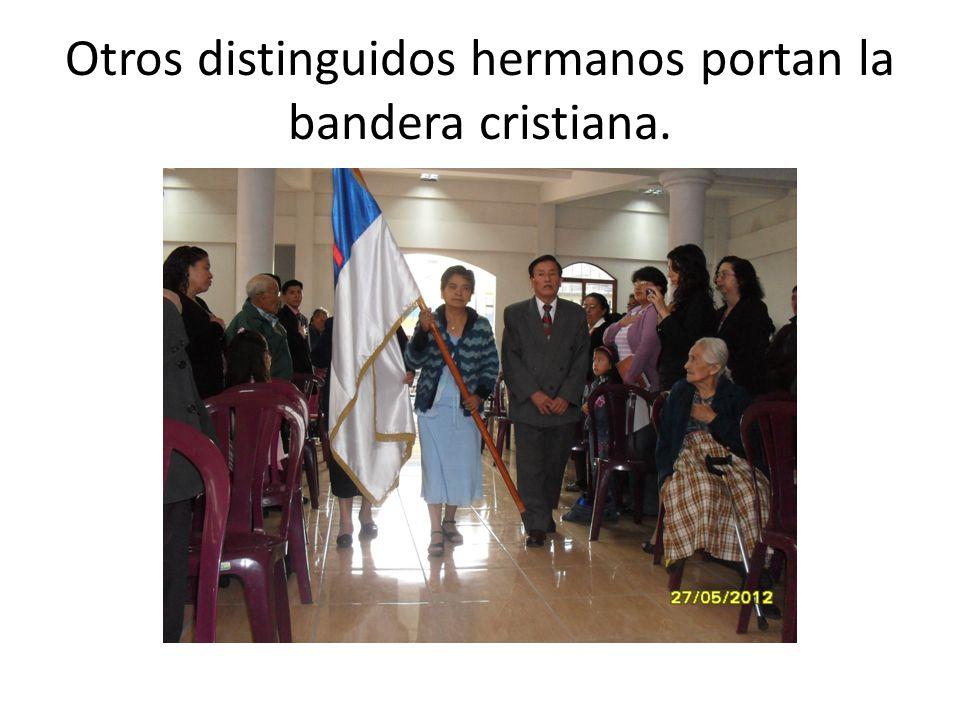 Otros distinguidos hermanos portan la bandera cristiana.