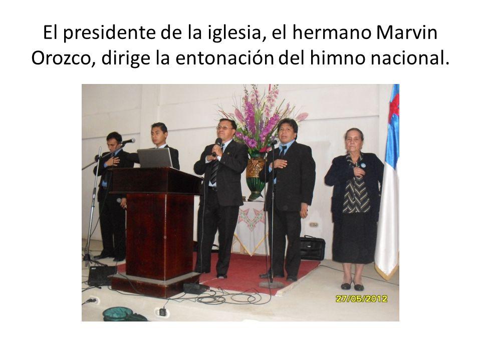 El presidente de la iglesia, el hermano Marvin Orozco, dirige la entonación del himno nacional.