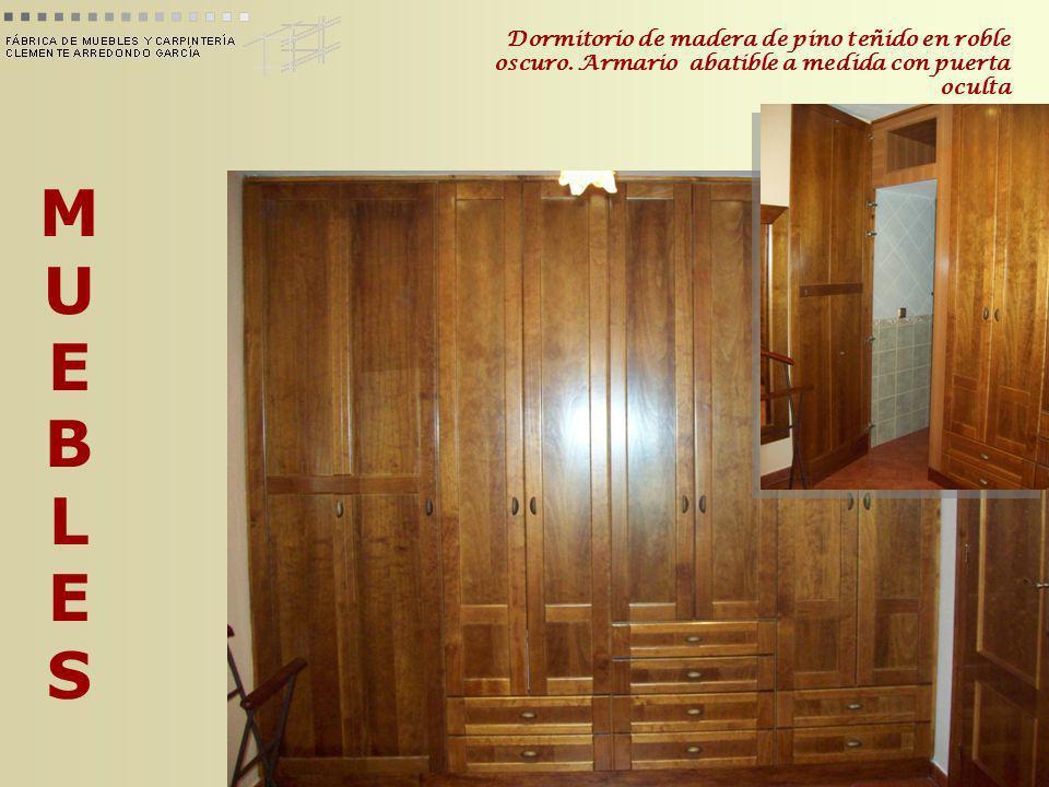 MUEBLESMUEBLES Dormitorio de madera de pino teñido en roble oscuro. Armario abatible a medida con puerta oculta