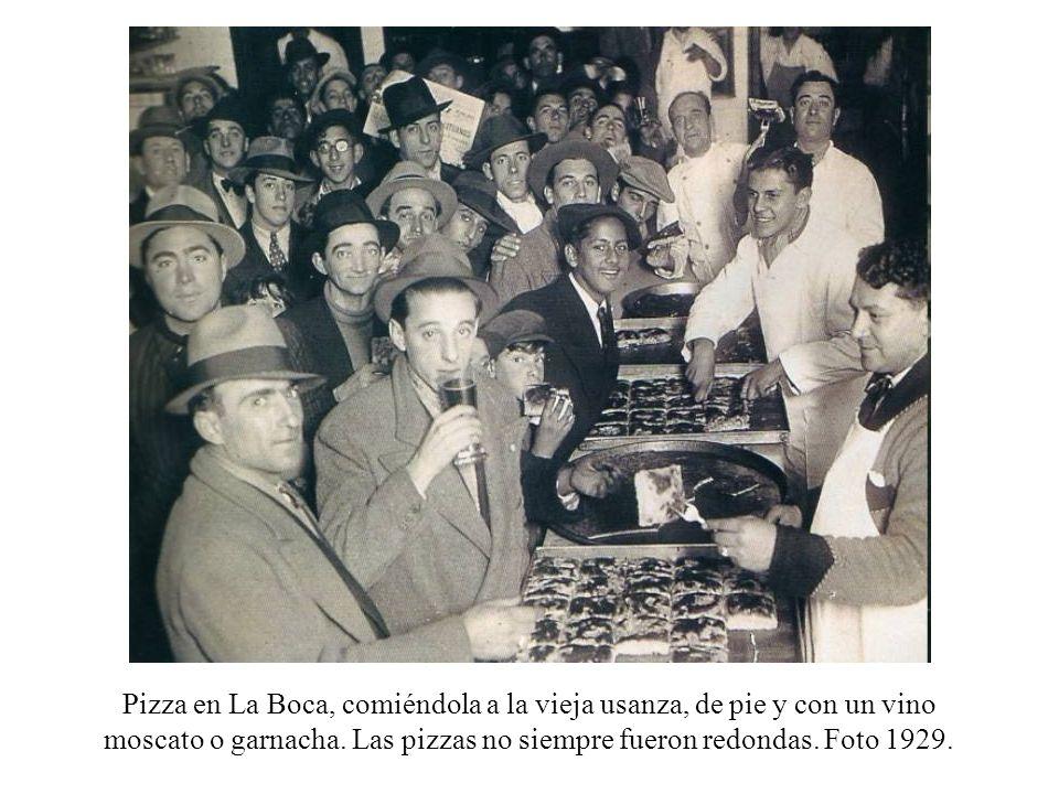 Pizza en La Boca, comiéndola a la vieja usanza, de pie y con un vino moscato o garnacha. Las pizzas no siempre fueron redondas. Foto 1929.