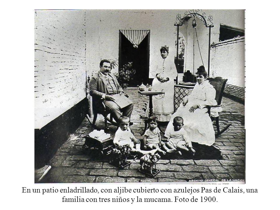 En un patio enladrillado, con aljibe cubierto con azulejos Pas de Calais, una familia con tres niños y la mucama. Foto de 1900.