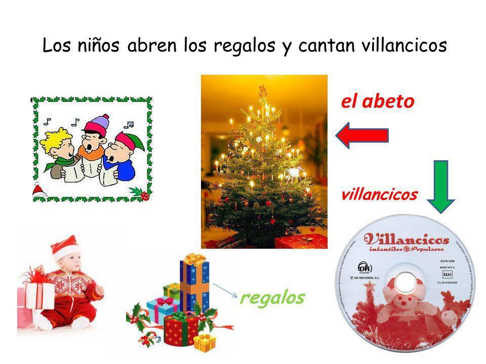 Los niños abren los regalos y cantan villancicos el abeto regalos villancicos