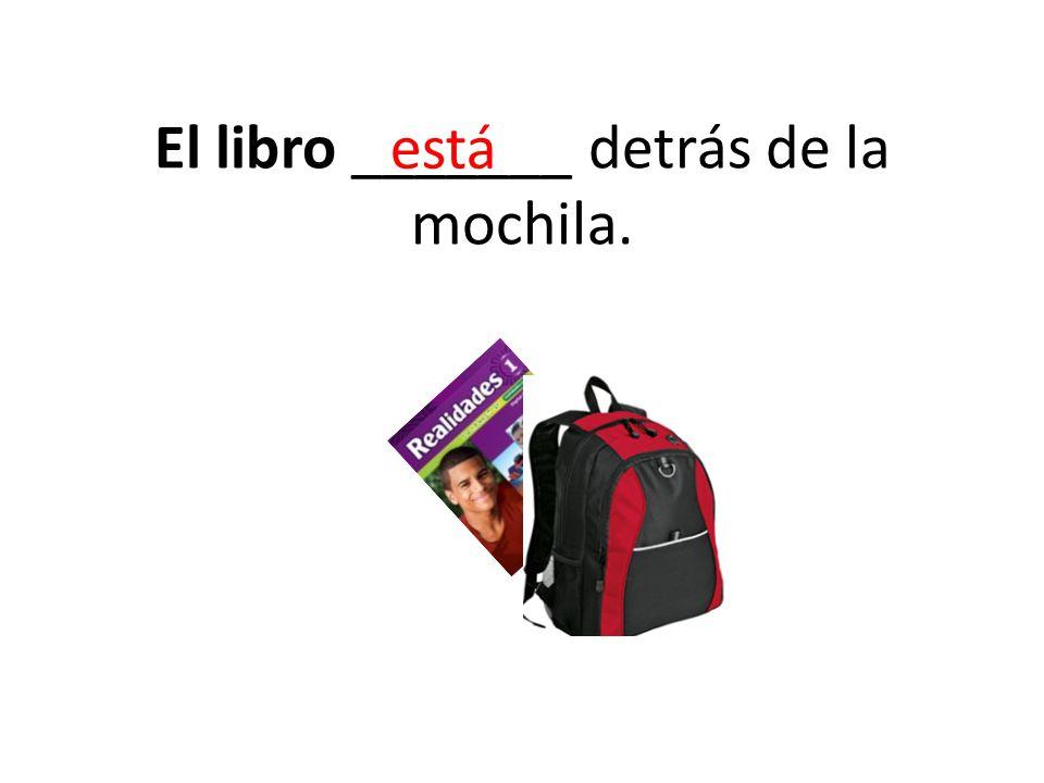 El libro _______ detrás de la mochila. está