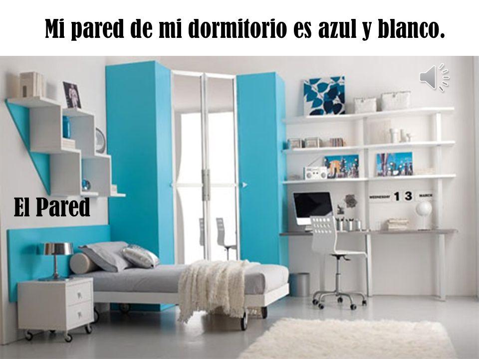 La cómoda esta a la derecha de la pupitre y es azul y blanco