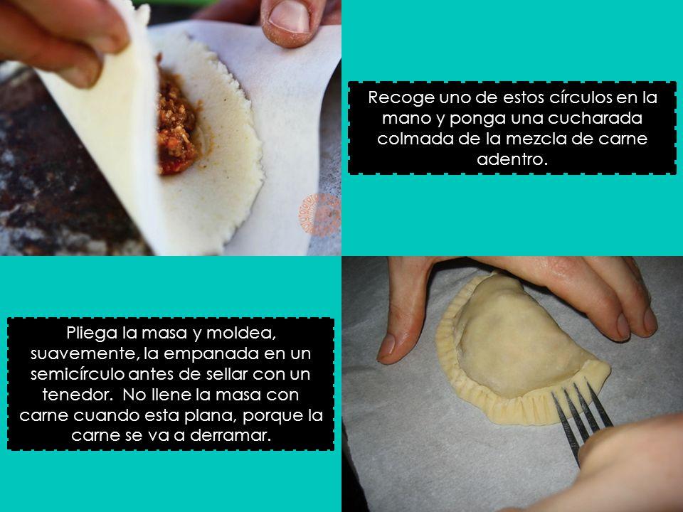 Recoge uno de estos círculos en la mano y ponga una cucharada colmada de la mezcla de carne adentro. Pliega la masa y moldea, suavemente, la empanada