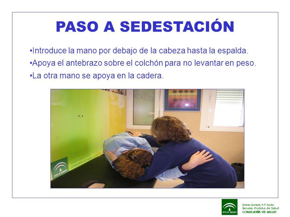 Introduce la mano por debajo de la cabeza hasta la espalda. Apoya el antebrazo sobre el colchón para no levantar en peso. La otra mano se apoya en la