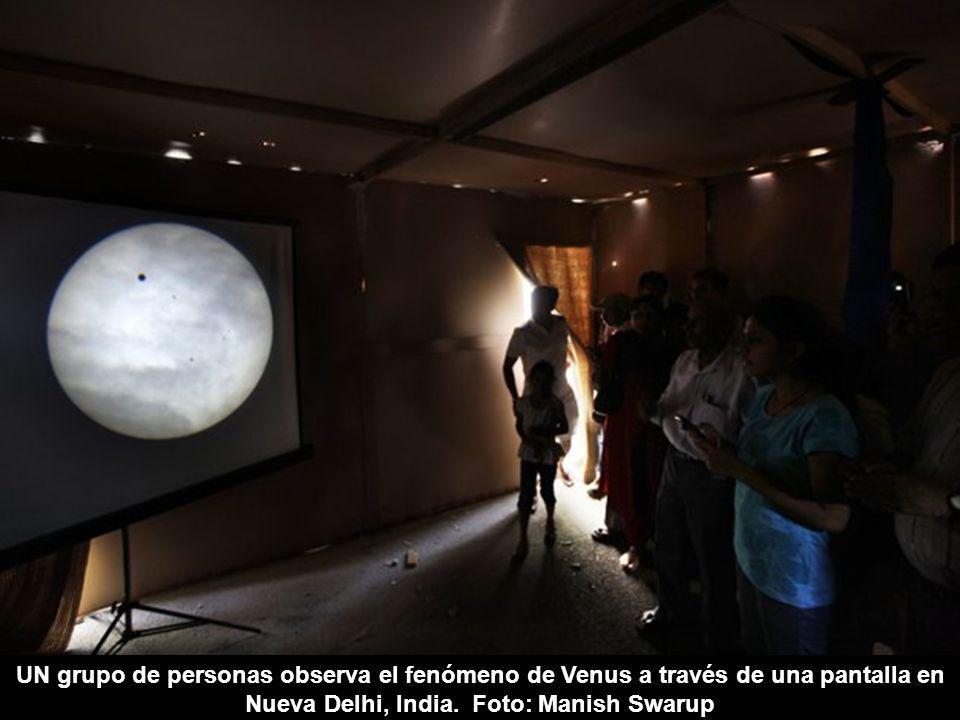UN grupo de personas observa el fenómeno de Venus a través de una pantalla en Nueva Delhi, India.