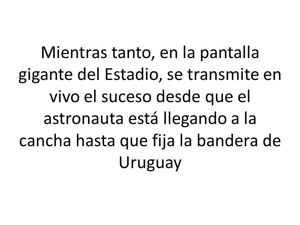 Mientras tanto, en la pantalla gigante del Estadio, se transmite en vivo el suceso desde que el astronauta está llegando a la cancha hasta que fija la bandera de Uruguay