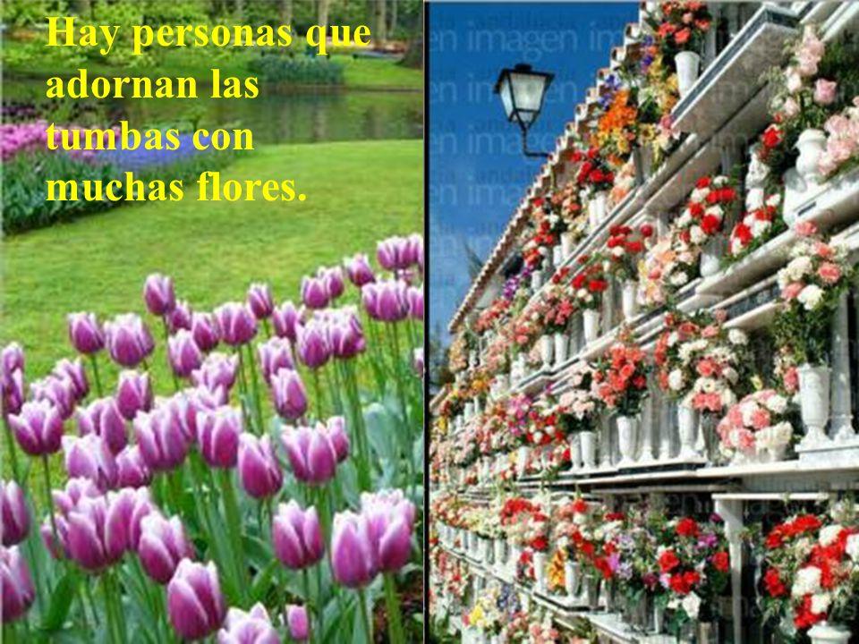 Hay personas que adornan las tumbas con muchas flores.