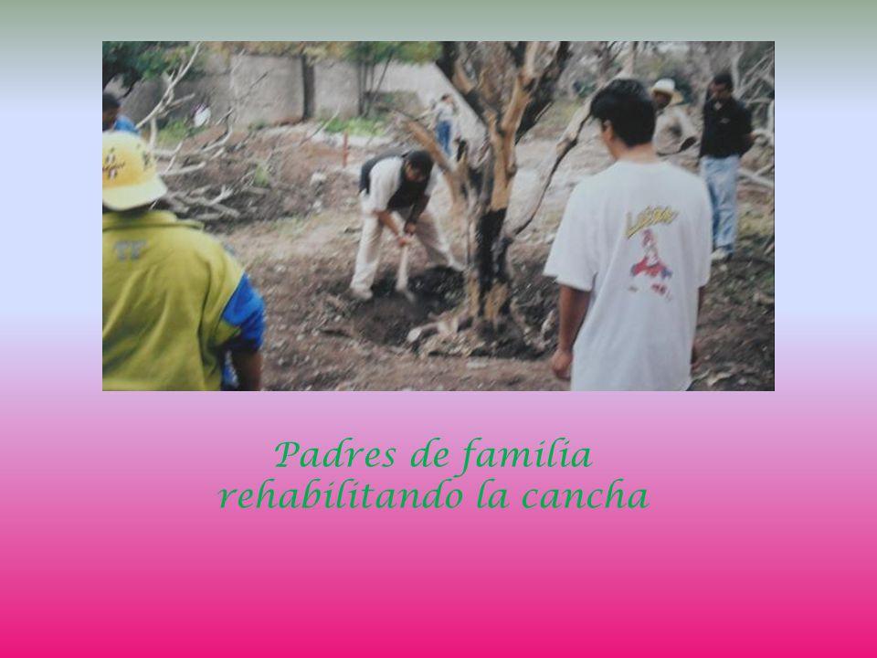 Padres de familia rehabilitando la cancha