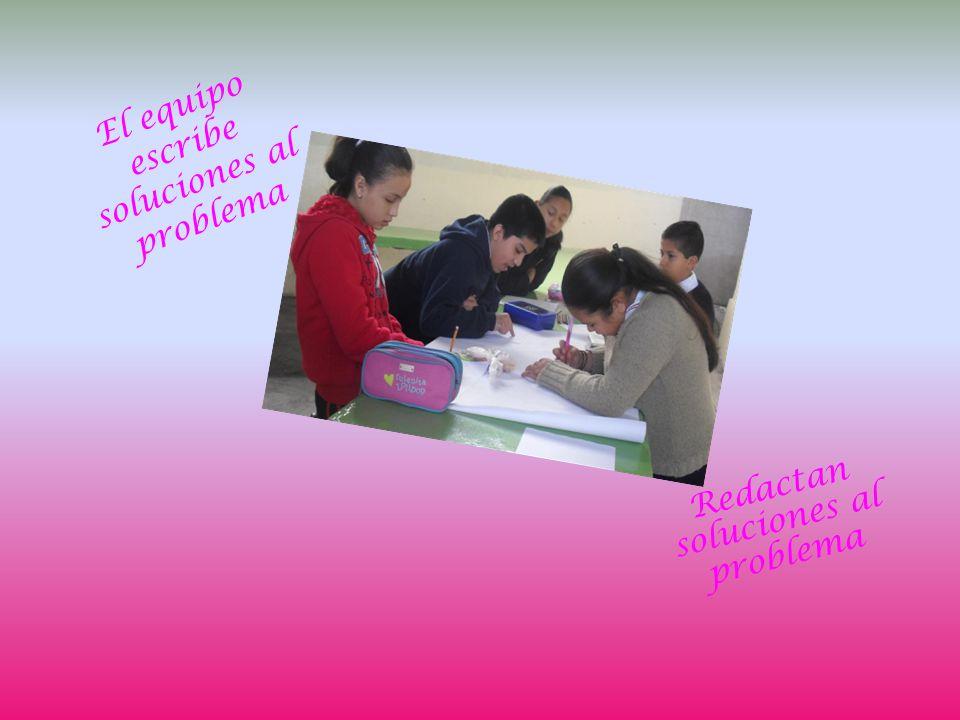 El equipo escribe soluciones al problema Redactan soluciones al problema