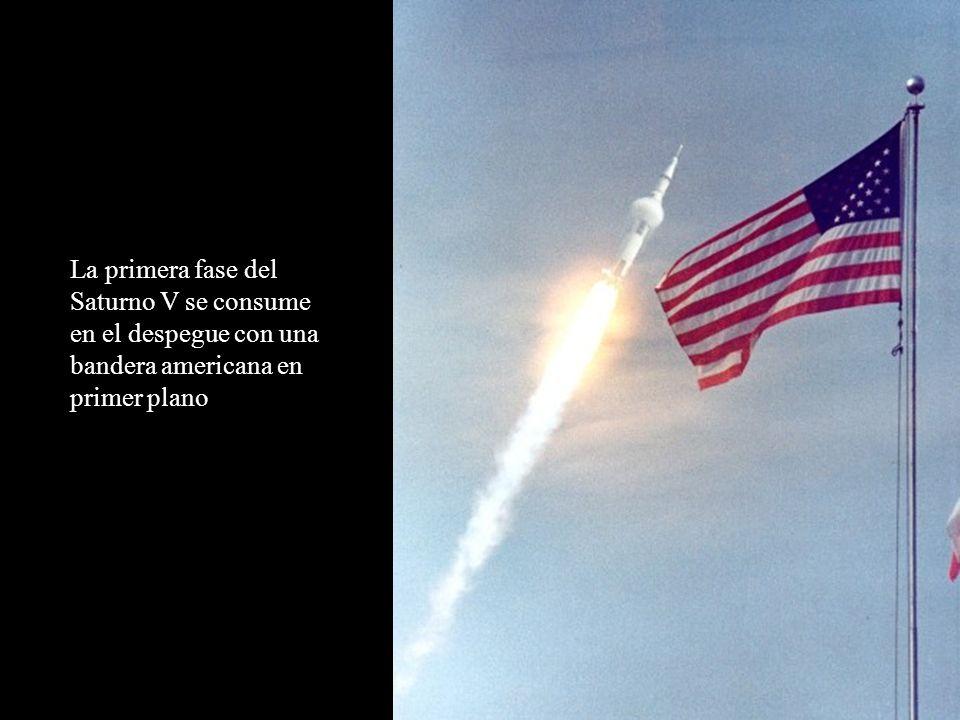 La primera fase del Saturno V se consume en el despegue con una bandera americana en primer plano