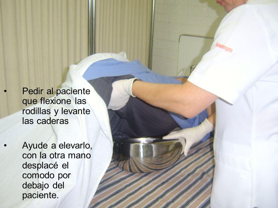 Pedir al paciente que flexione las rodillas y levante las caderas Ayude a elevarlo, con la otra mano desplacé el comodo por debajo del paciente.